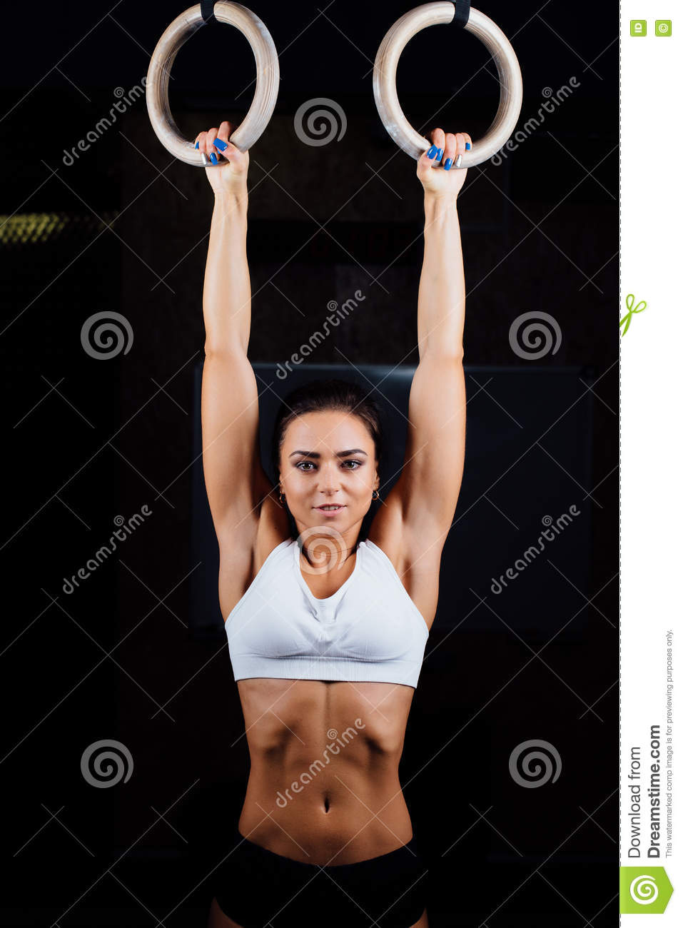 Crossfit. Portrait of young fit muscular girl in white top using gymnastic