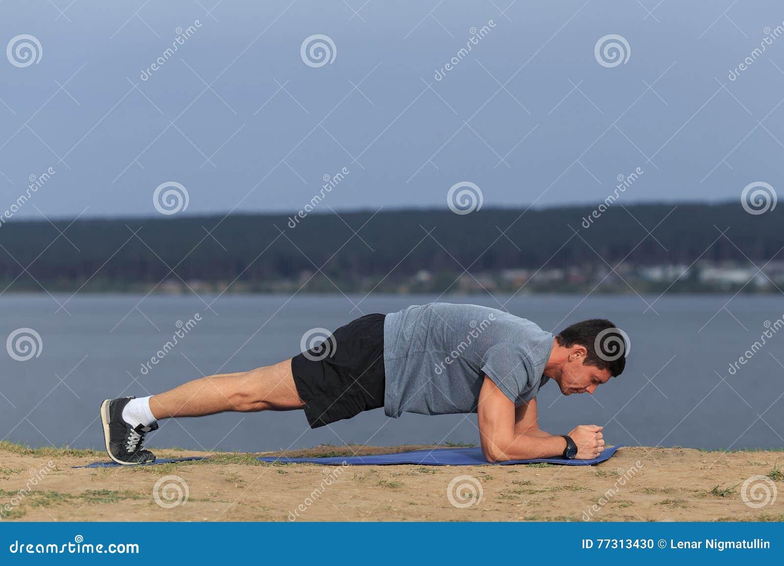 Crossfit sprawności fizycznej stażowy mężczyzna robi deski sedna ćwiczeniu pracującemu out jego midsection sedna mięśnie