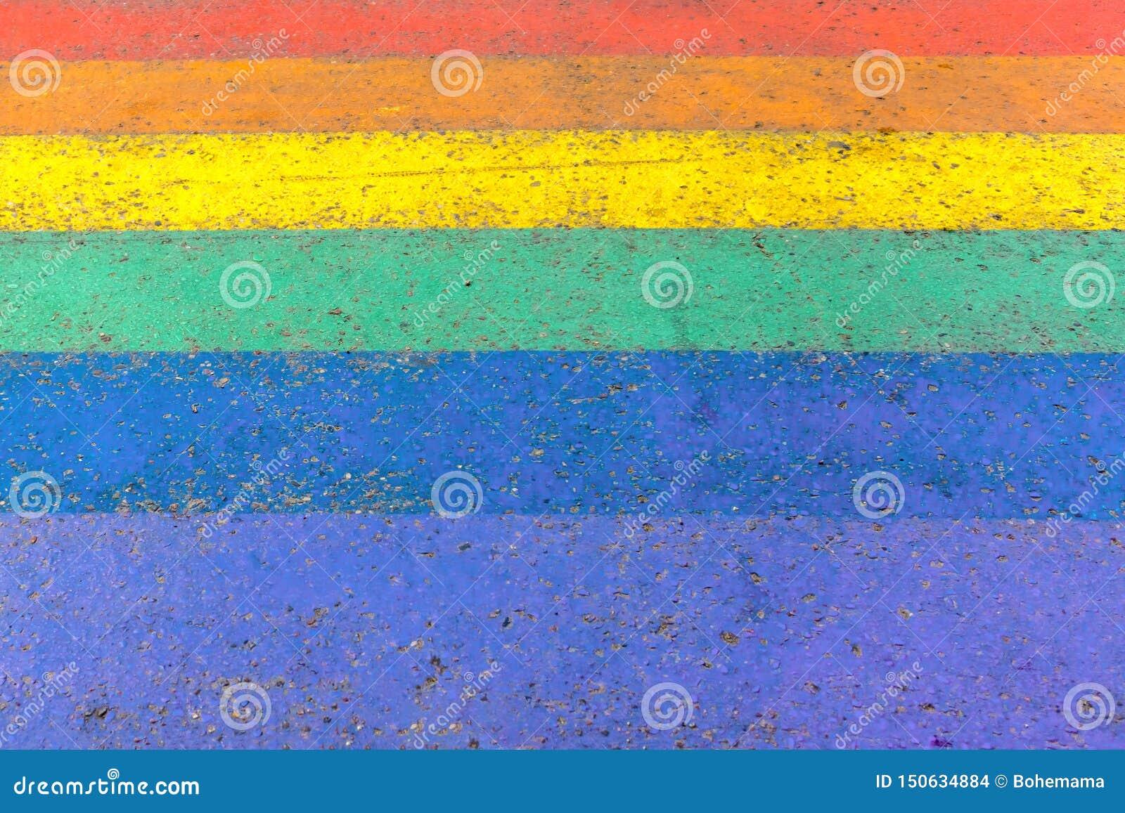 Crossing in street of LGBTQI or LGBT rainbow pride flag colors as background