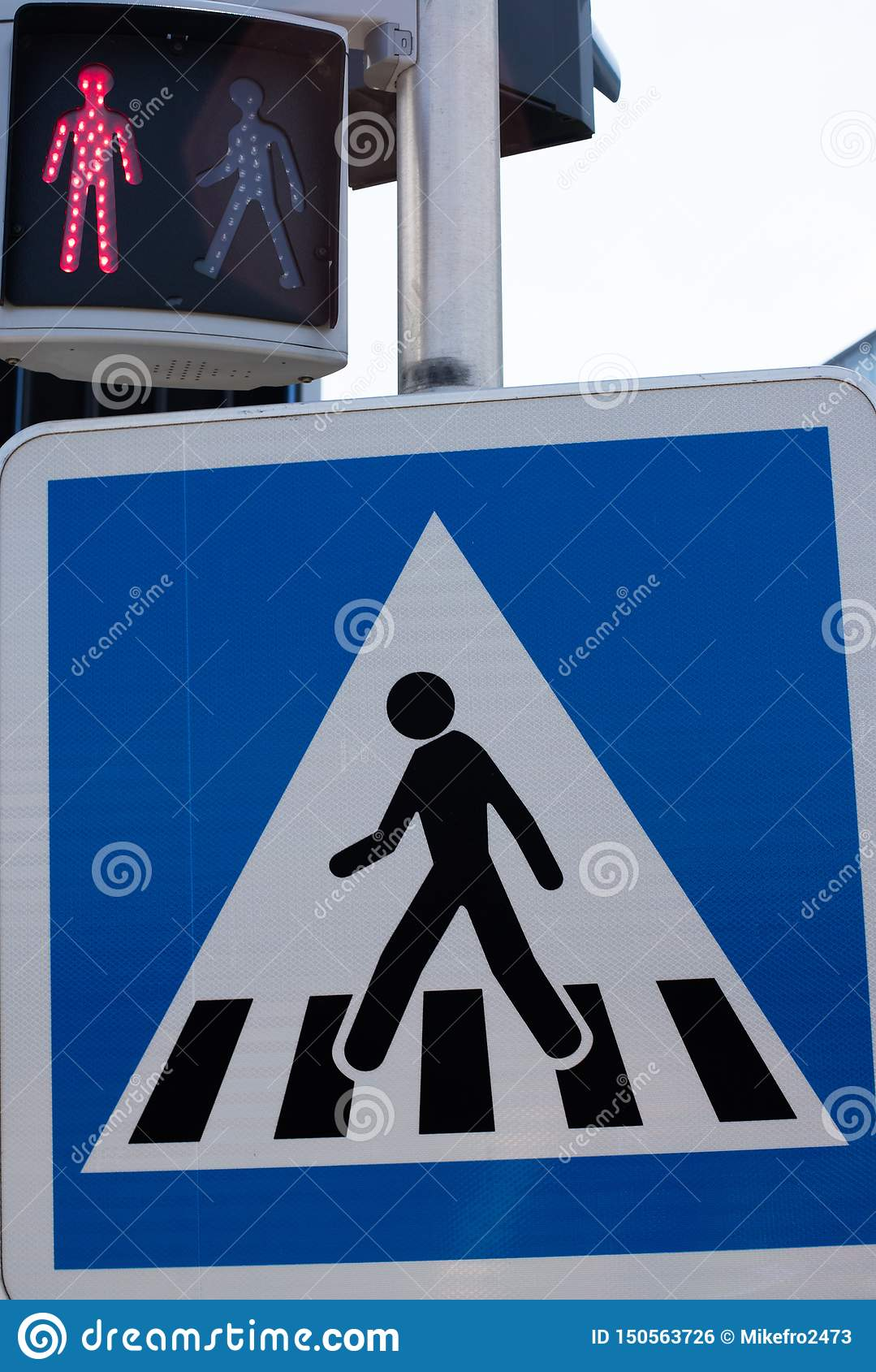 Crosswalk road sign. Pedestrian crossing sign and traffic light for pedestrians. Red light no passage. Standing man