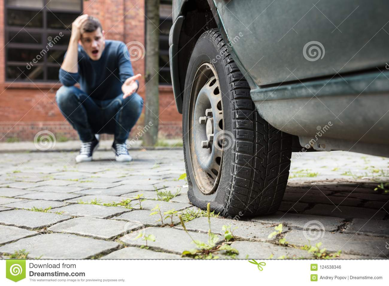 Crouched Man Pointing At Punctured Car Tire