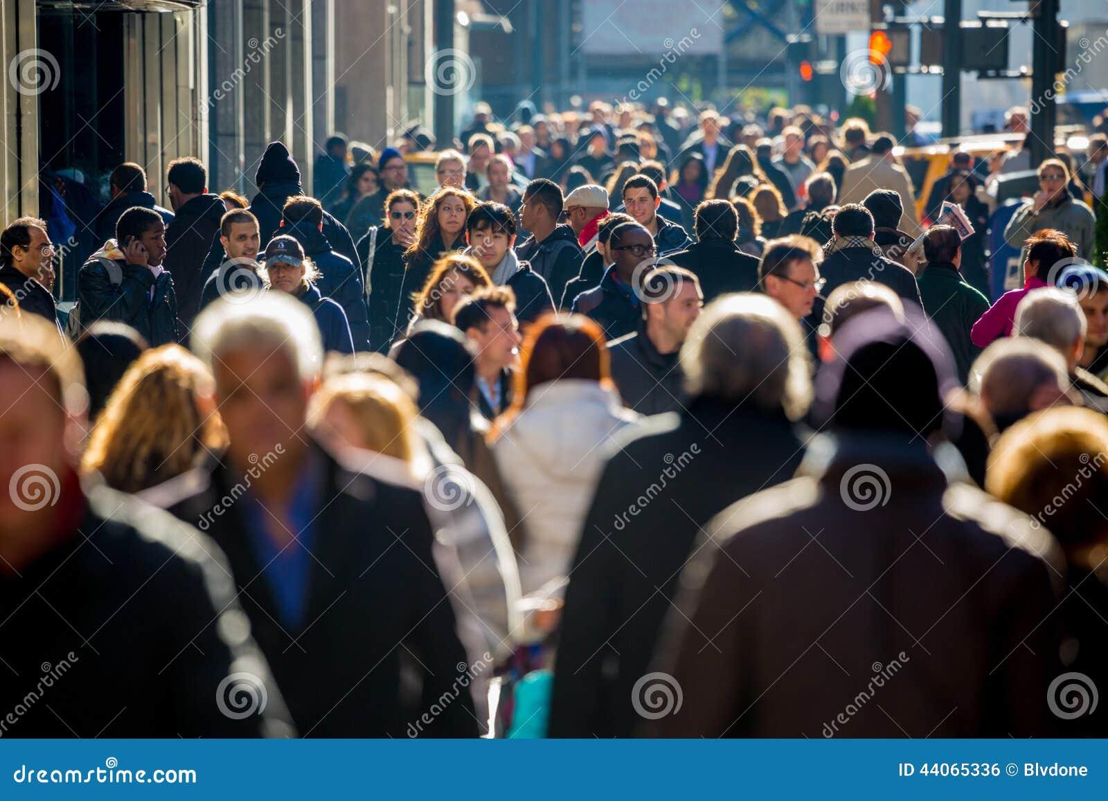Crowd of people walking on street sidewalk