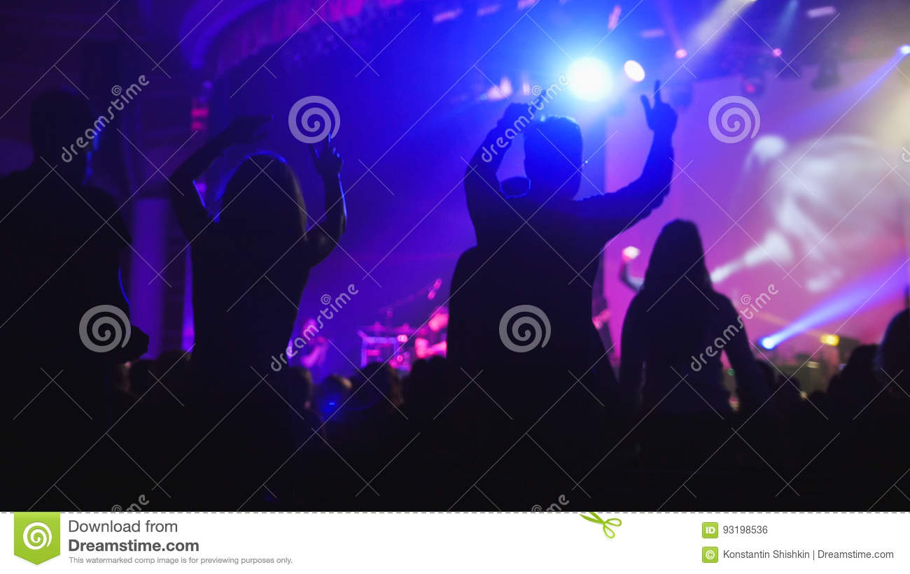 The crowd of shadows of people dancing at the concert