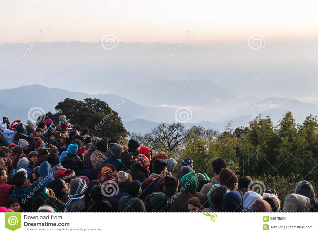 Crowded people are waiting for the first light in the dawn of new year`s  day with mountain and fog in background at Tiger Hill, Darjeeling. India.