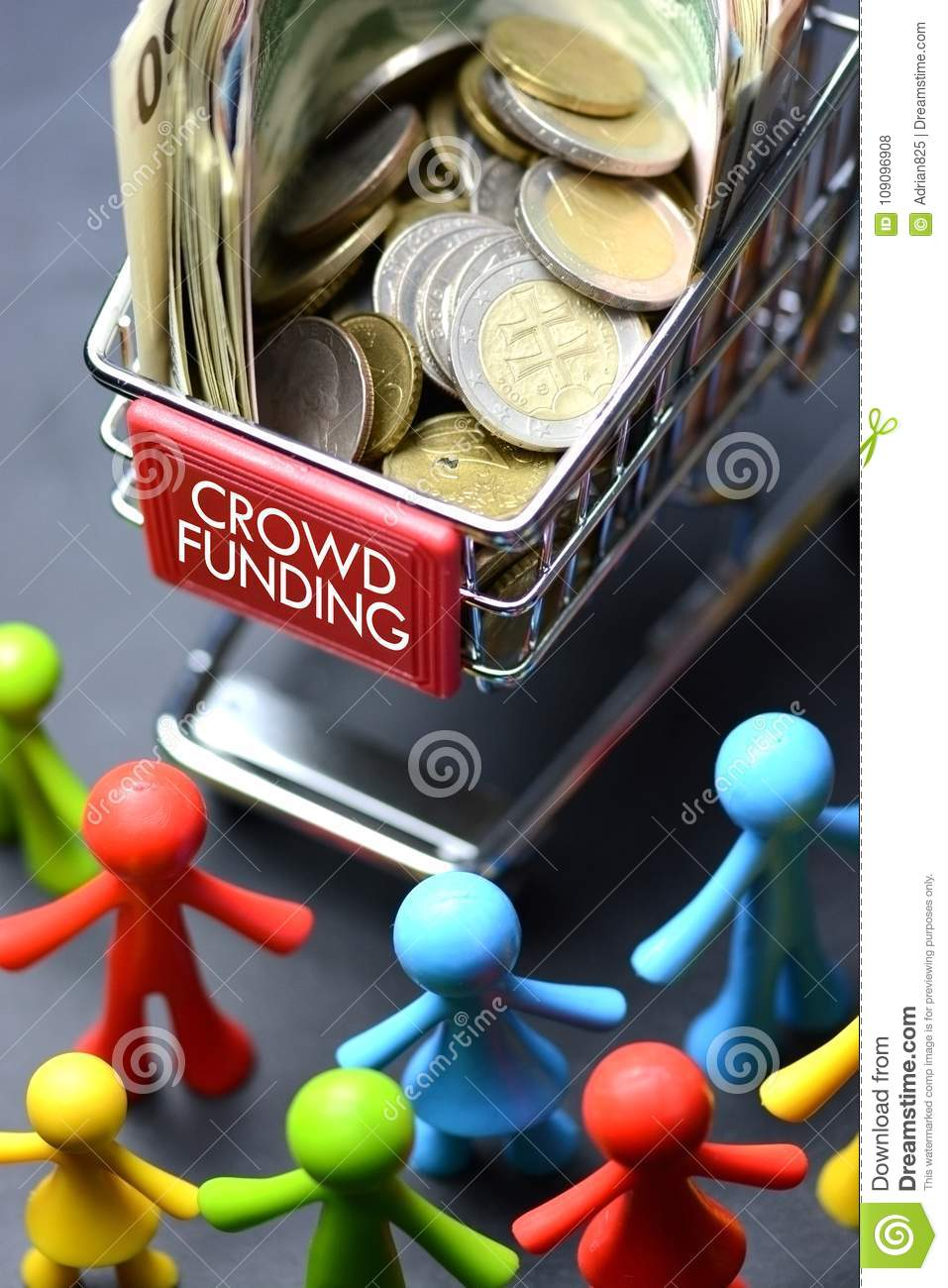 Crowdfunding concept with multicolored figurine and shopping trolley full of money on dark background