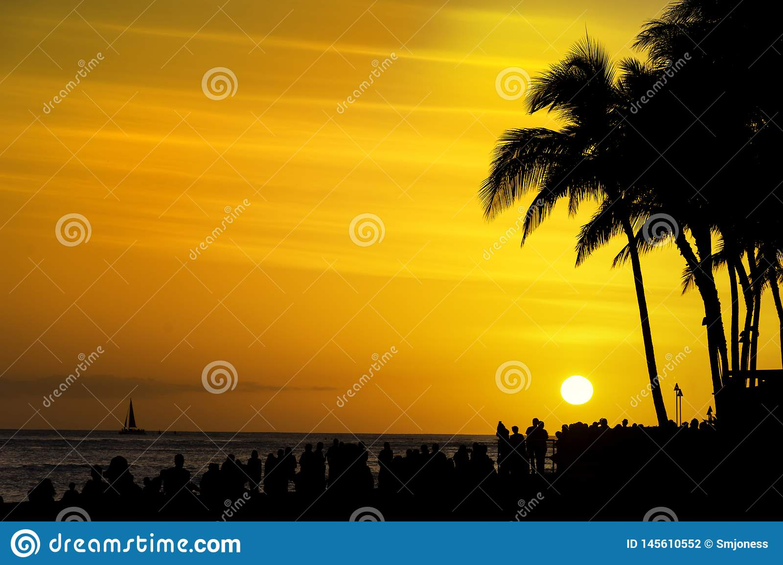 Crowds Of Tourists Gather To Watch The Sunset On Waikiki