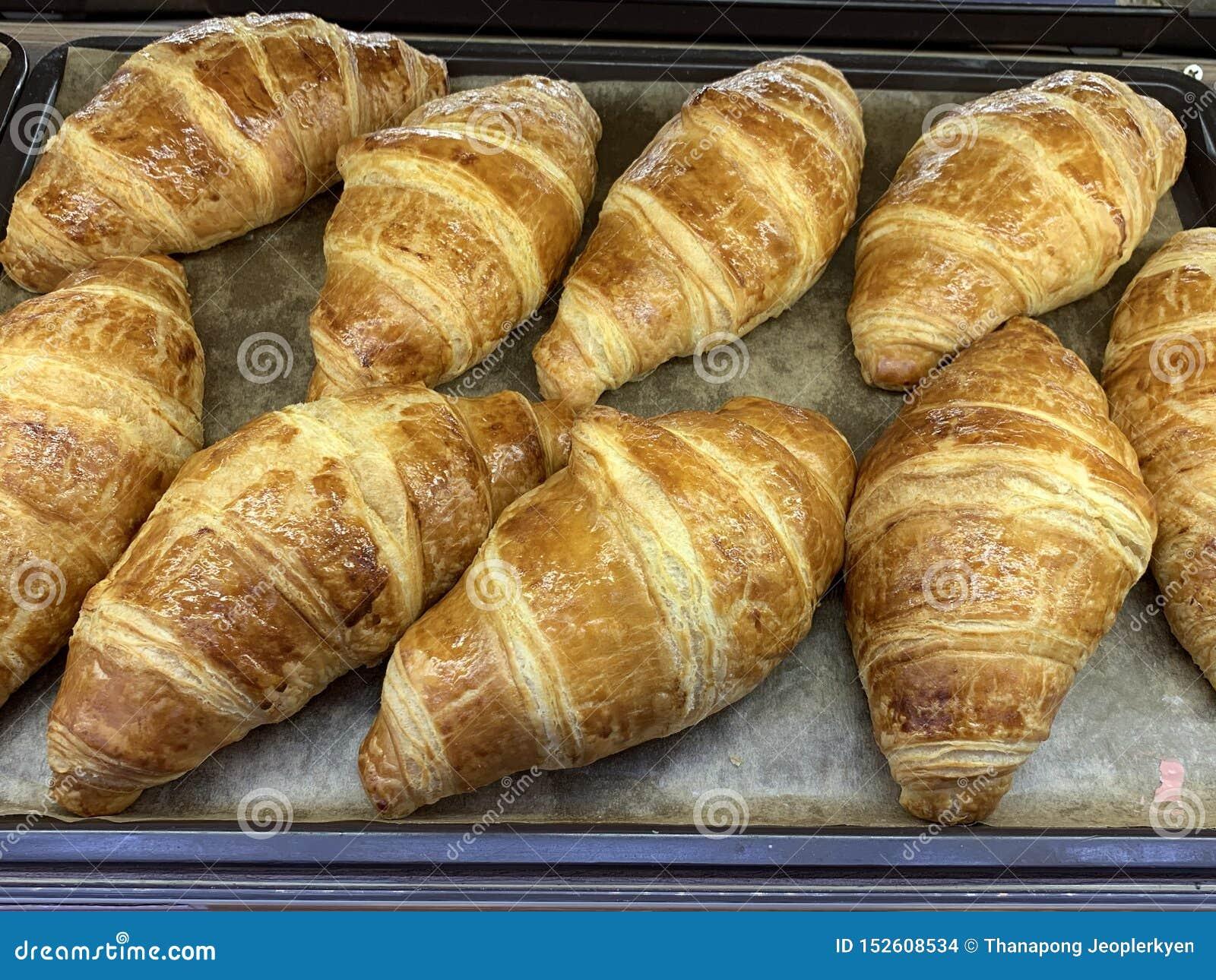 Cruasanes recientemente cocidos en la comida de la bandeja