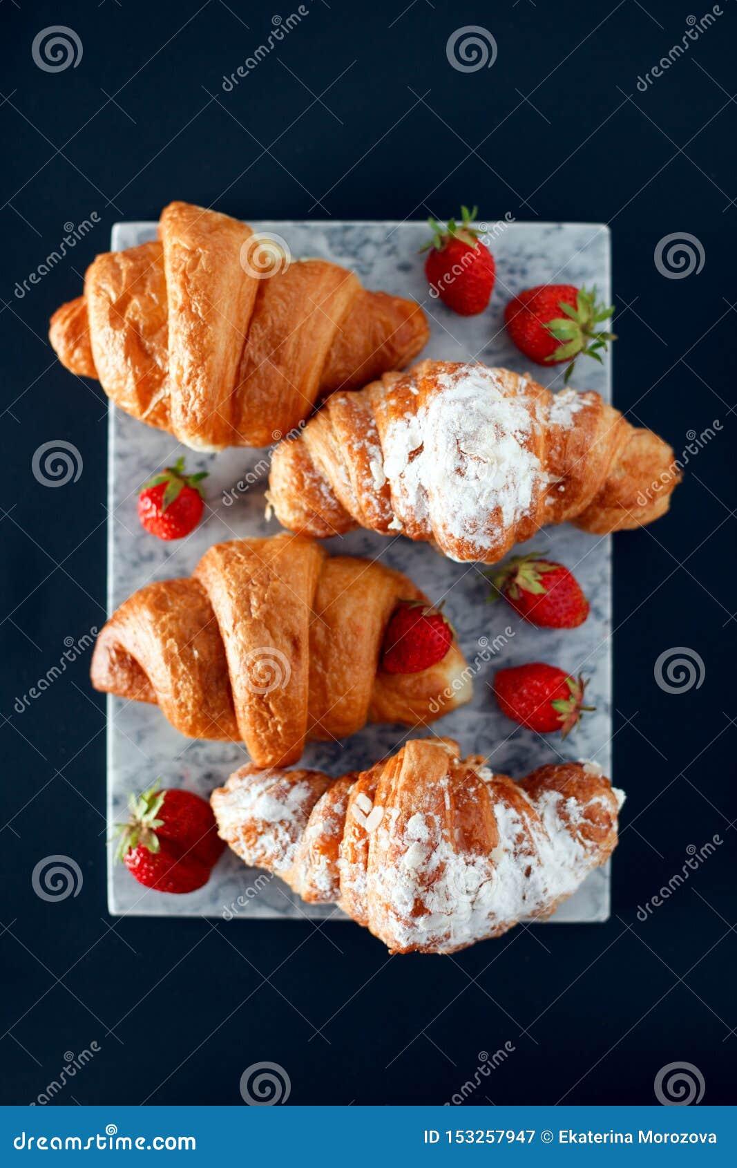 Cruasanes recientemente cocidos en la tabla de cortar de mármol, visión superior, espacio de la copia, fondo del desayuno
