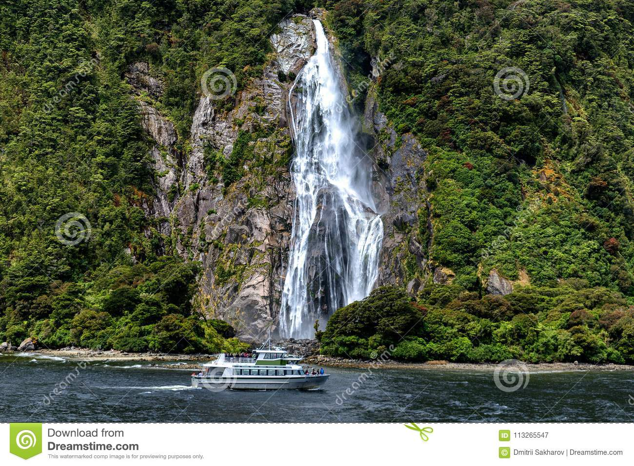 Cruise Ferry And Beautiful High Waterfall In Milford Sound