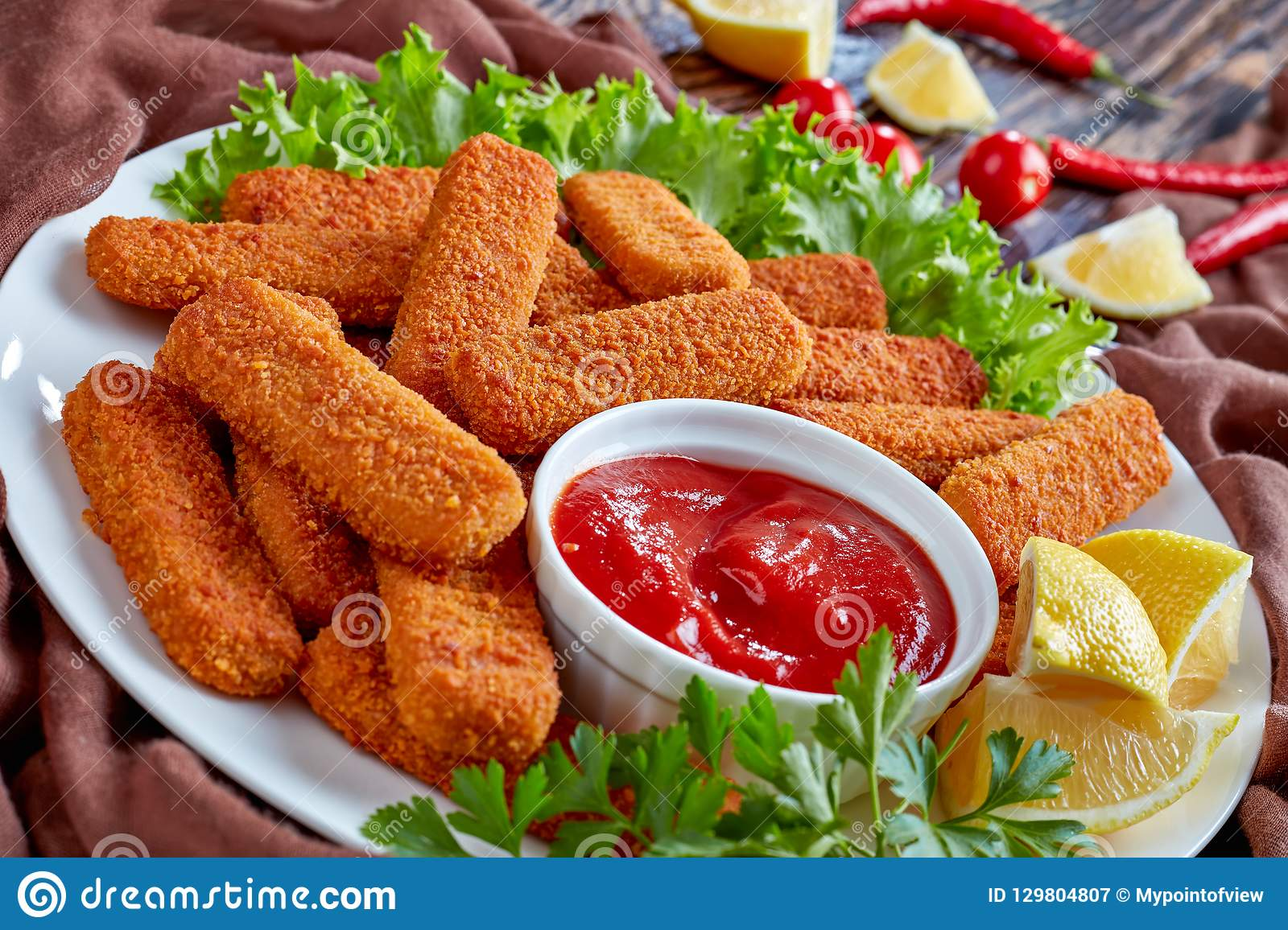 Crumbed fish sticks served with ketchup