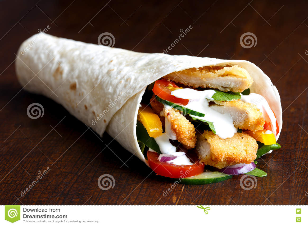Crumbed fried chicken and salad tortilla wrap with white sauce i