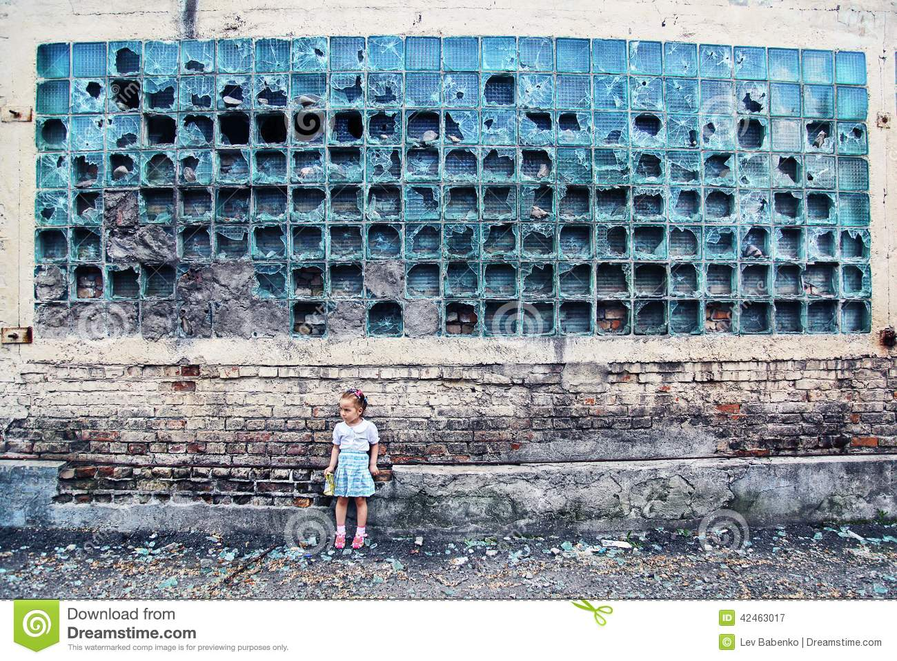 Crumbling wall. broken glass, little defenseless girl