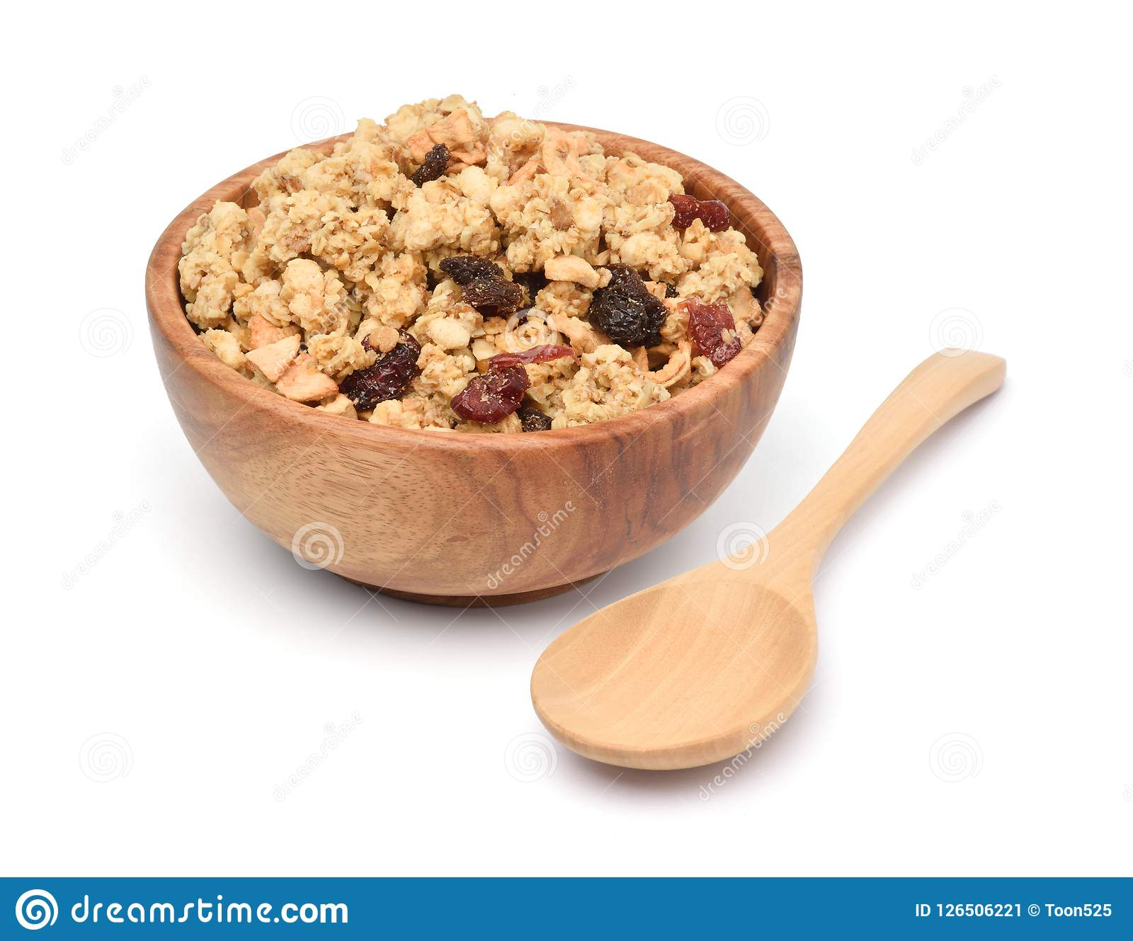 Crunchy oat granola cereal with dried fruits in wooden bowl