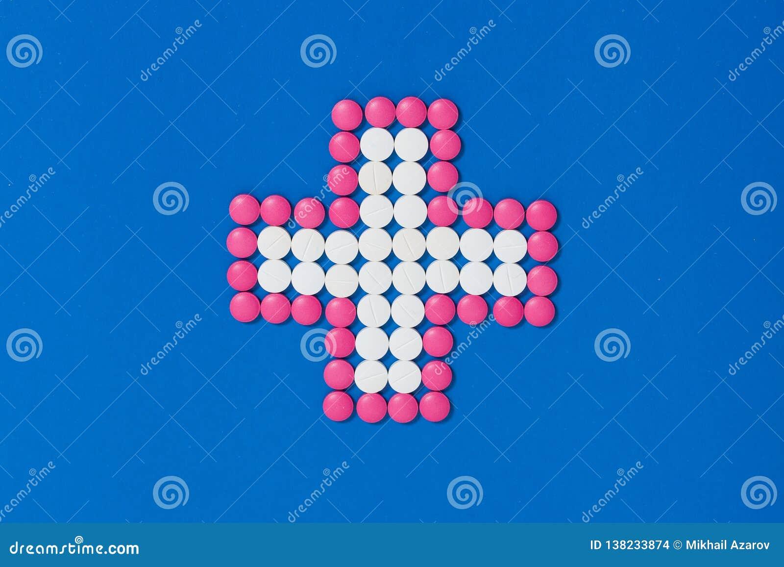 Cruz de las píldoras del rosa y blancas en fondo azul