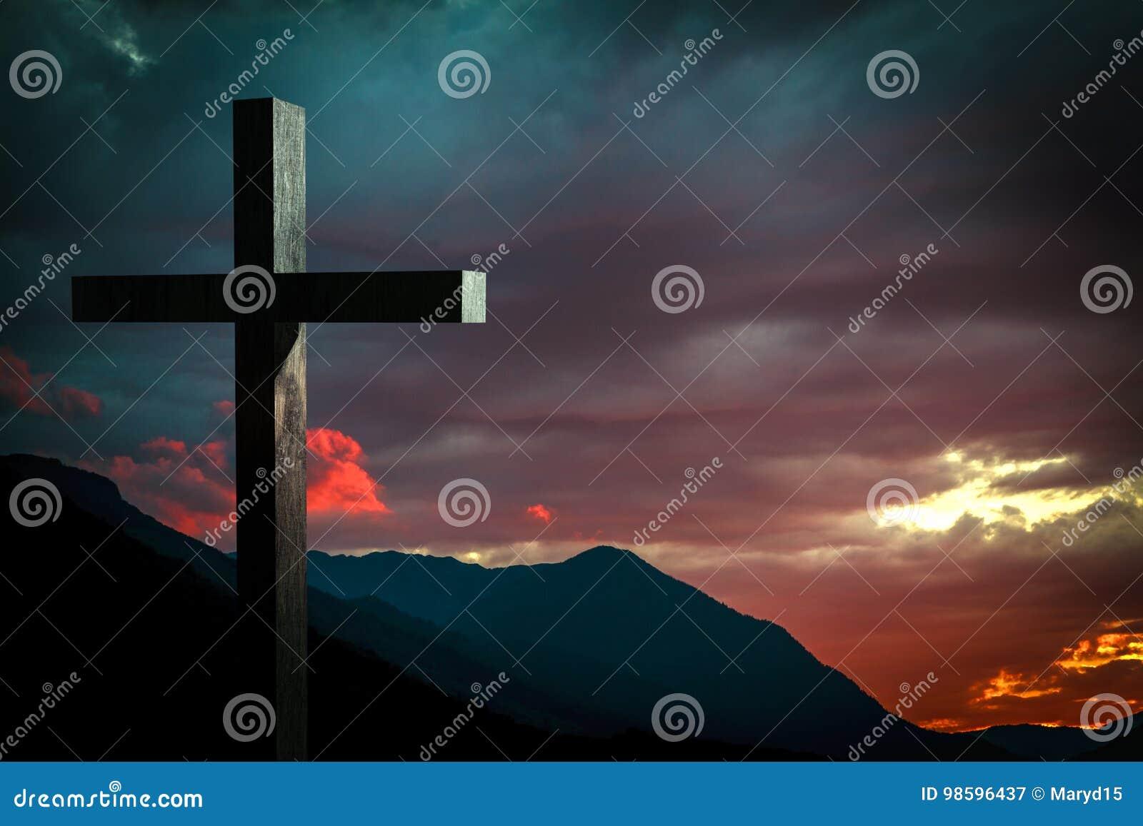 Cruz de madera de Jesus Christ en una escena con el cielo dramático y la puesta del sol colorida, salida del sol
