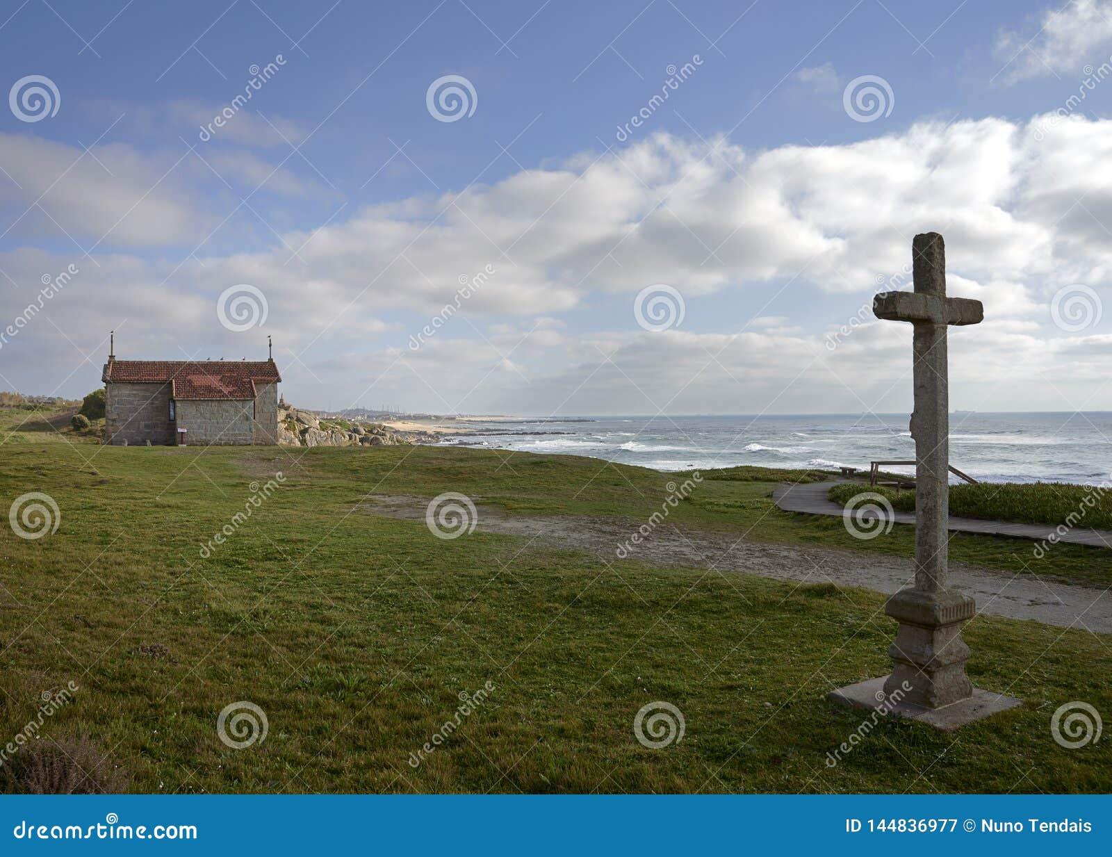 Cruz e iglesia en Castro de São Paio, pasando por alto la playa