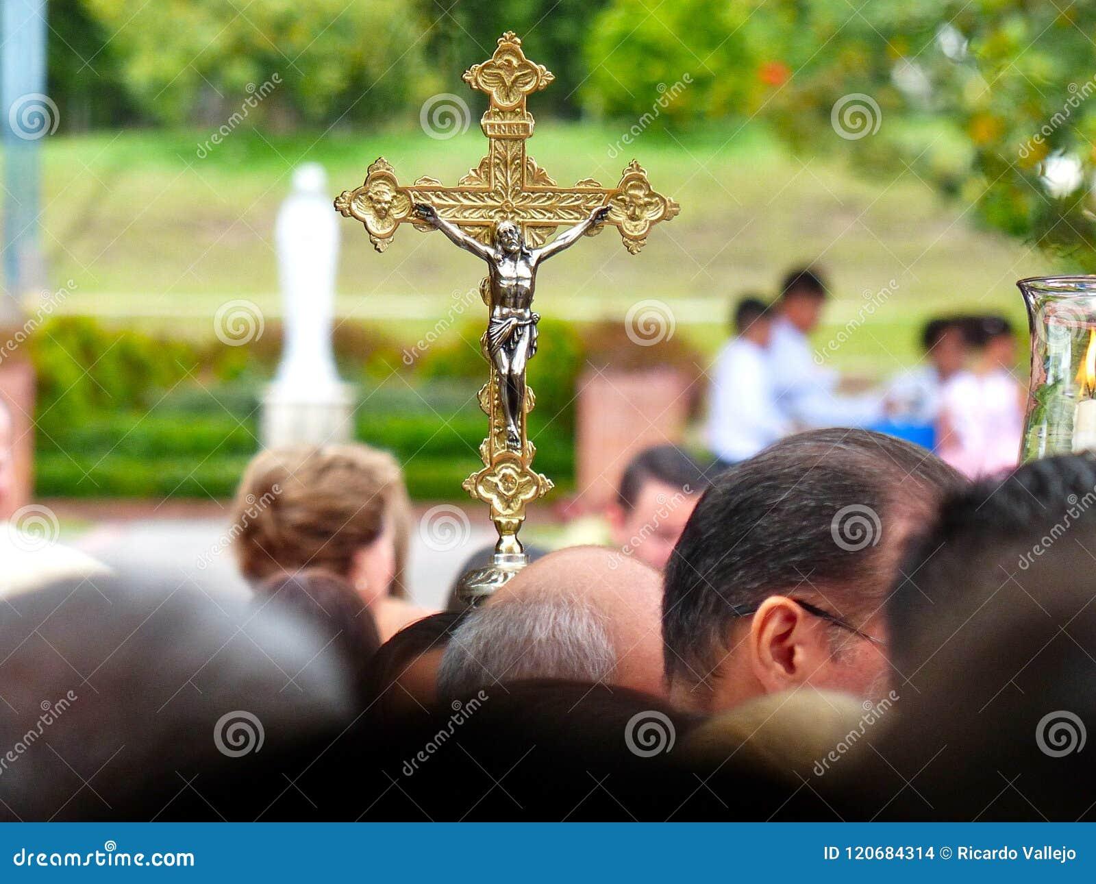 Cruz santamente dourada acima das cabeças dos povos com fundo borrado
