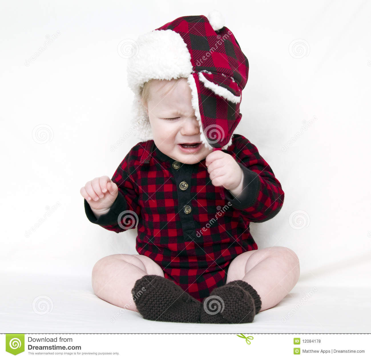 Crying Christmas Baby Trying To Pull Off Hat Stock Photo