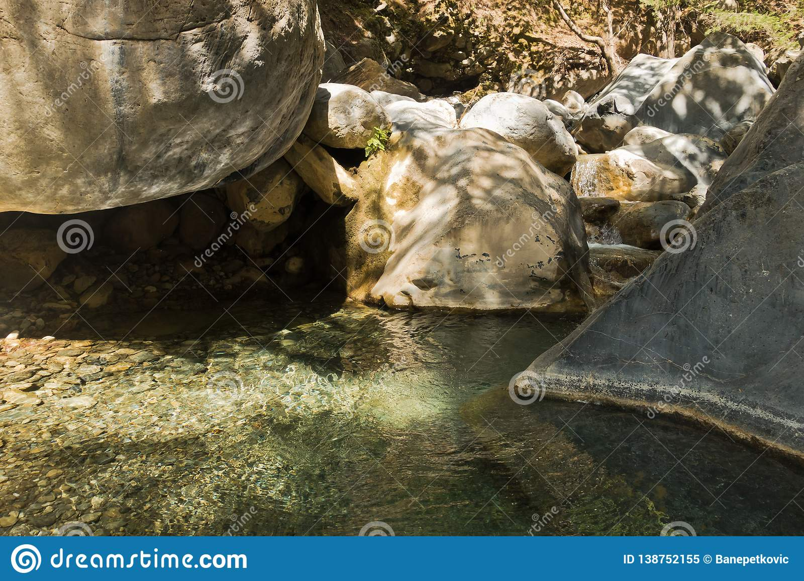 Crystal Clear Water Of A Cold Mountain Creek At Rocky Terrain Of