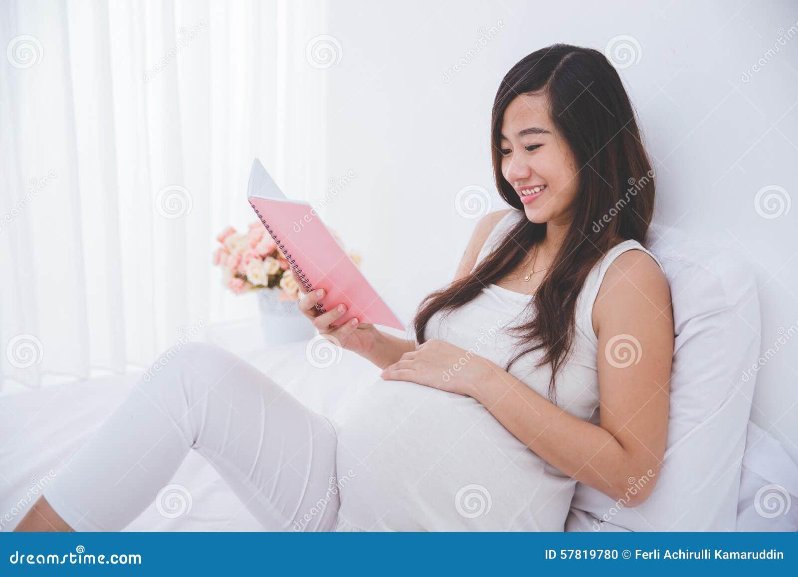 Cuaderno asiático embarazada hermoso de la lectura de la mujer, sonriendo