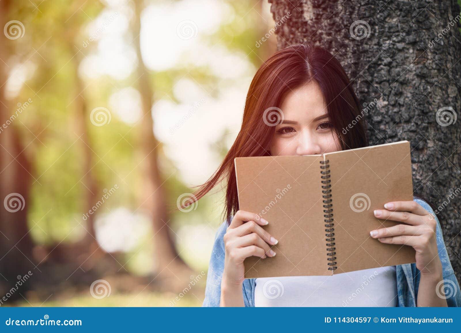 Cuaderno asiático hermoso de la lectura de la mujer