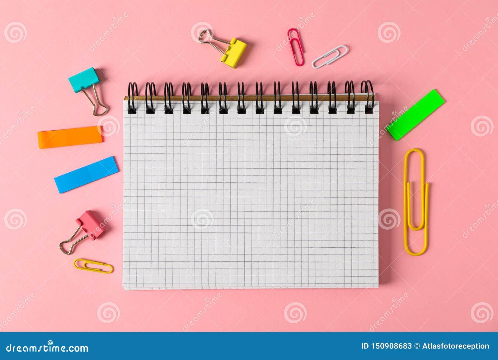 Cuaderno, clips y etiquetas engomadas en fondo del color