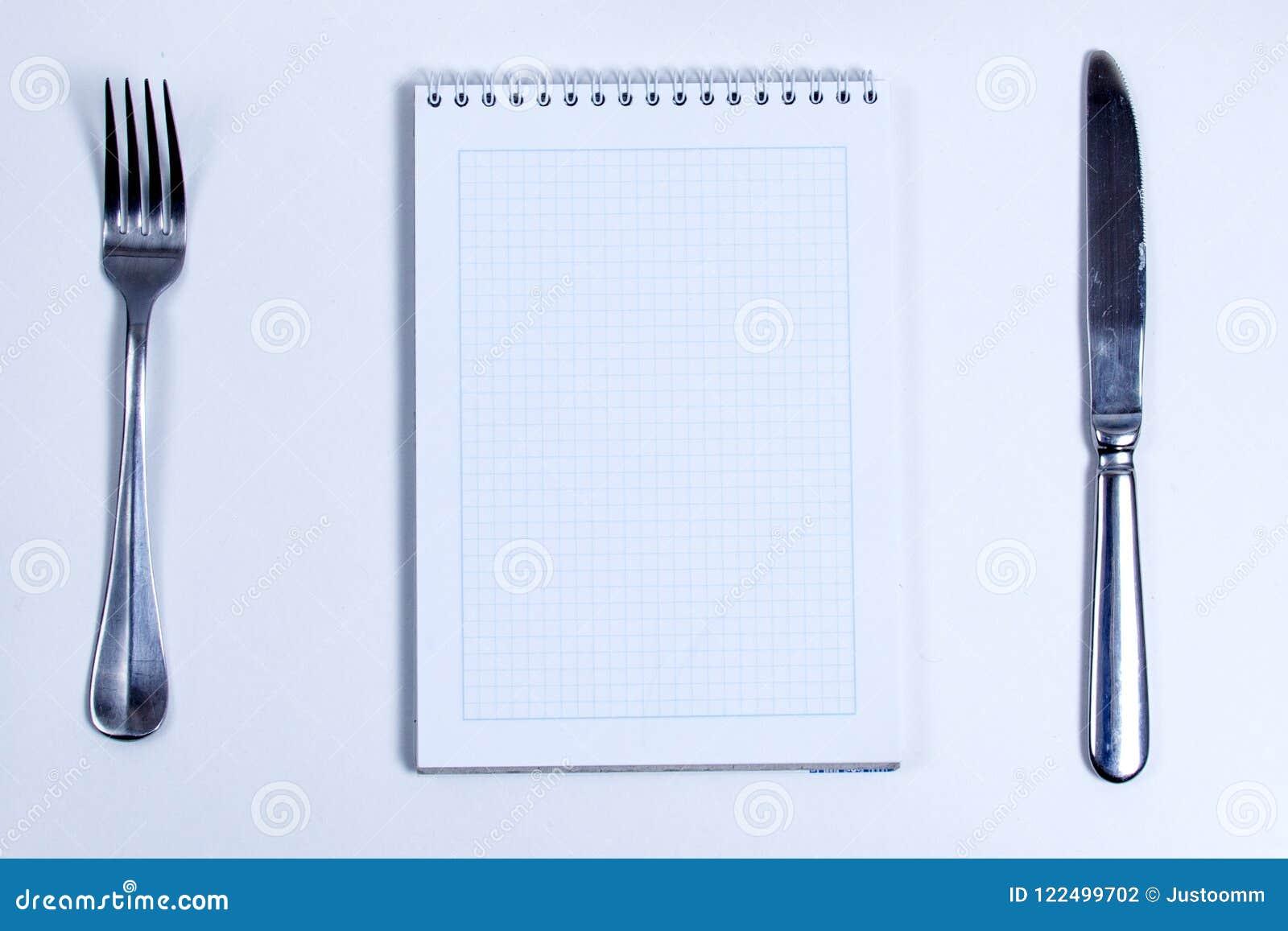 Cuaderno con los cubiertos de plata Cuaderno en blanco alineado con espiral y cubiertos de la plata, bifurcación y cuchillo