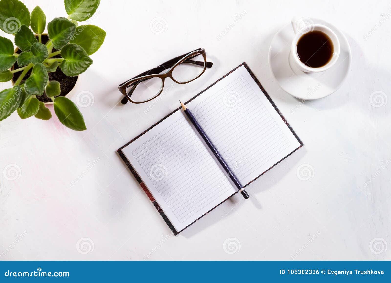Cuaderno con los vidrios y el café en la tabla