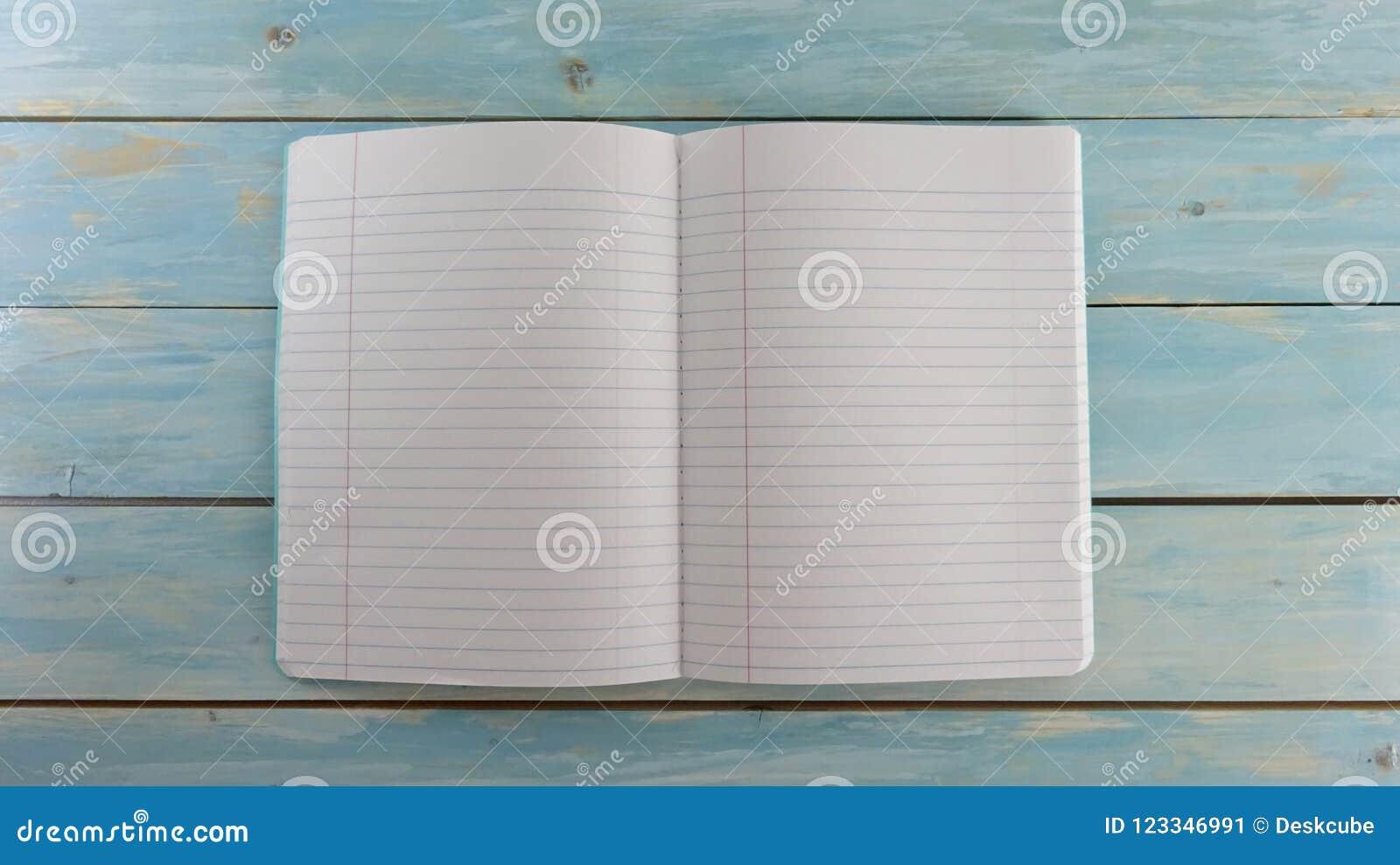 Cuaderno de la escuela en el fondo de madera azul del tablero - bandera de la educación