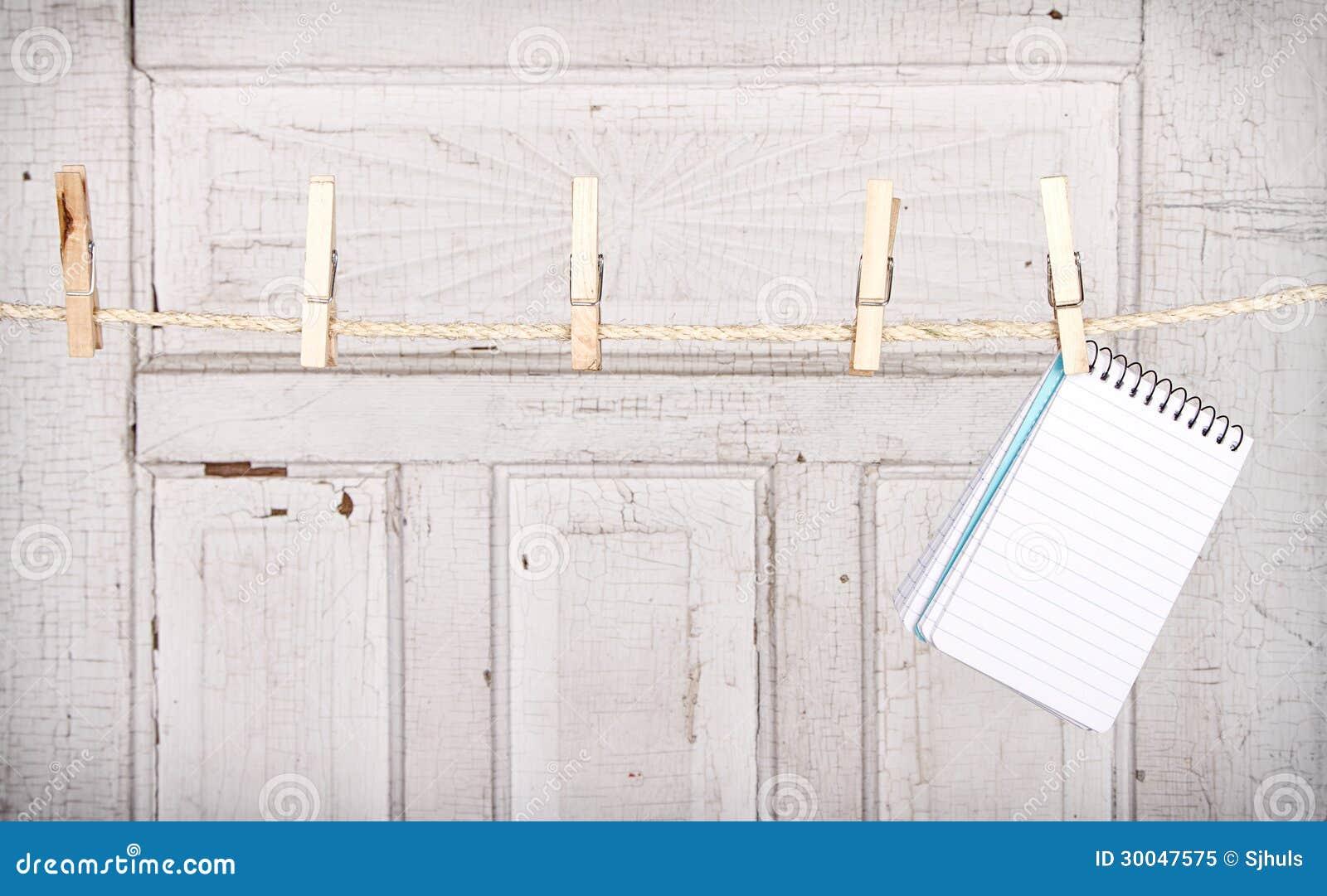 Cuaderno de notas que cuelga de una línea de ropa