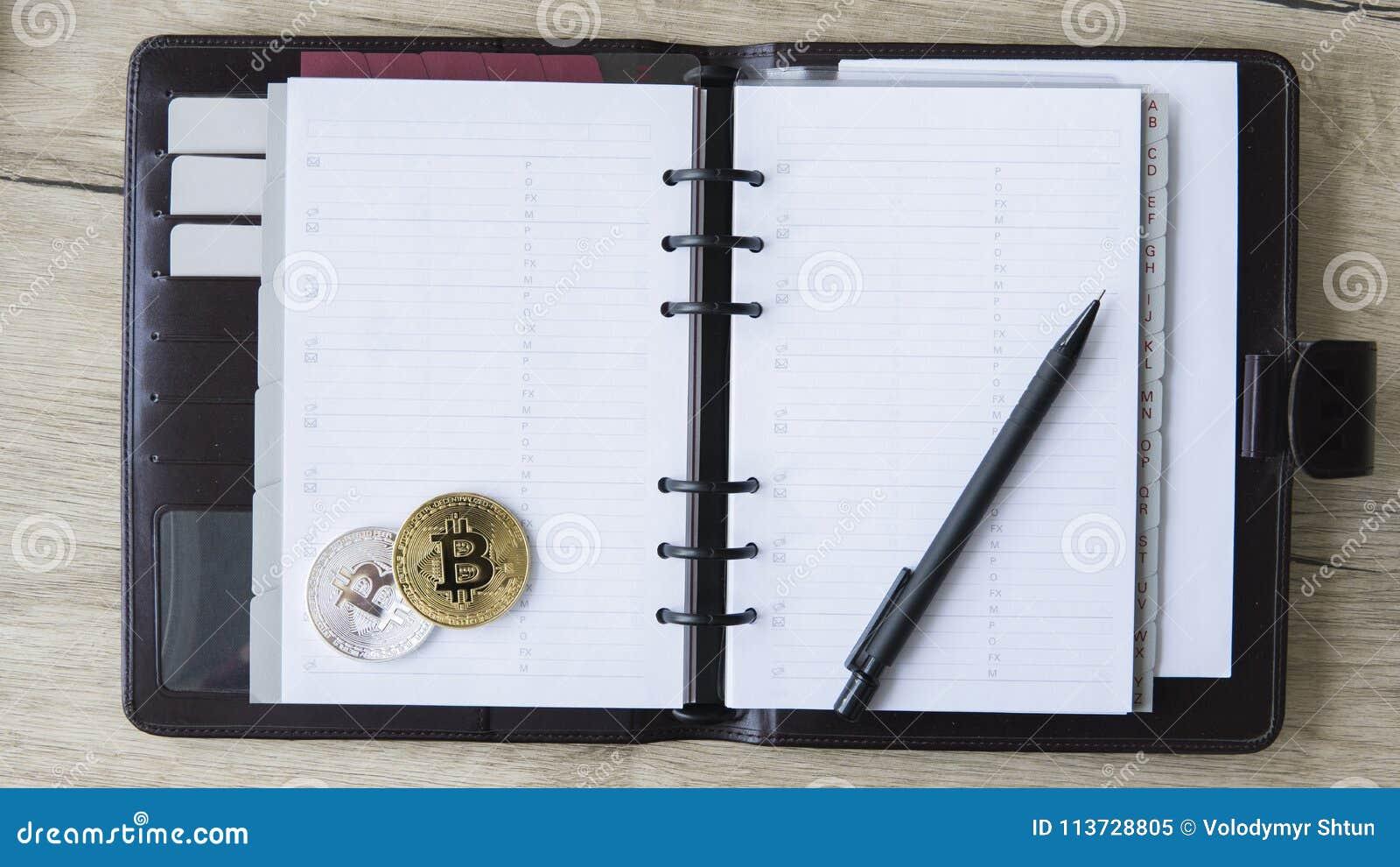 Cuaderno del minero de Bitcoin Oro y plata Bitcoin y pluma en un cuaderno abierto El espacio libre para puso un texto en las pági