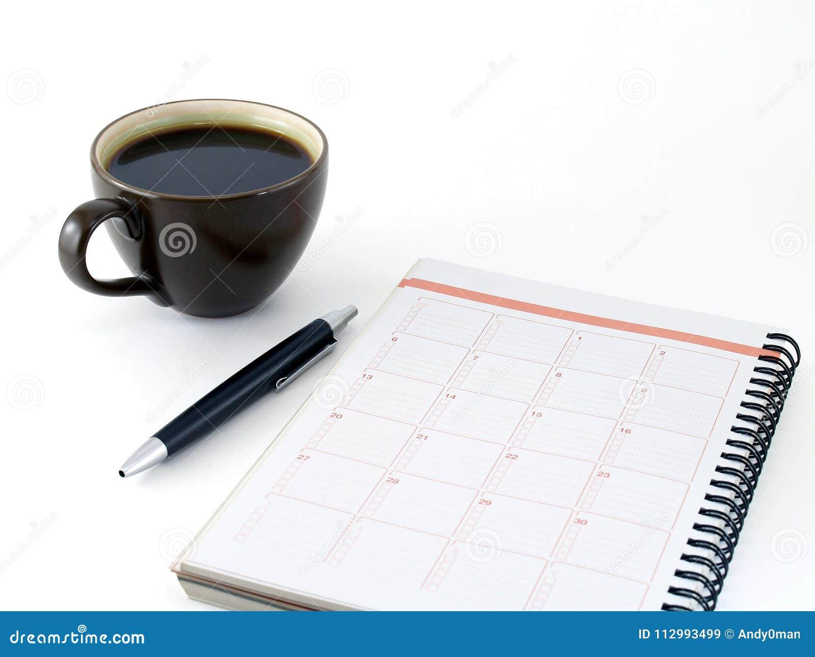 Cuaderno del primer, pluma negra y café caliente en la taza de cerámica del marrón oscuro aislada en el fondo blanco