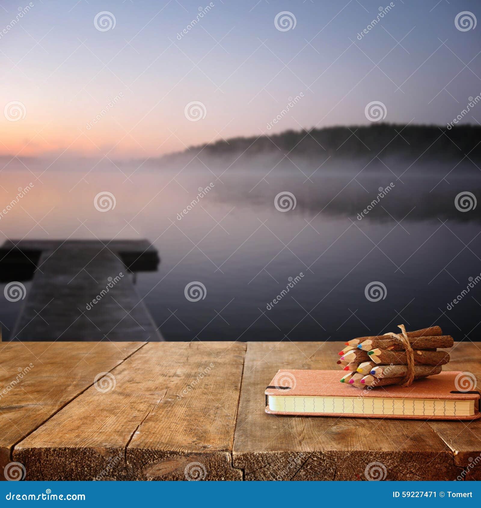 Cuaderno del vintage y pila de lápices coloridos de madera en la tabla de madera de la textura delante de la opinión de niebla tr