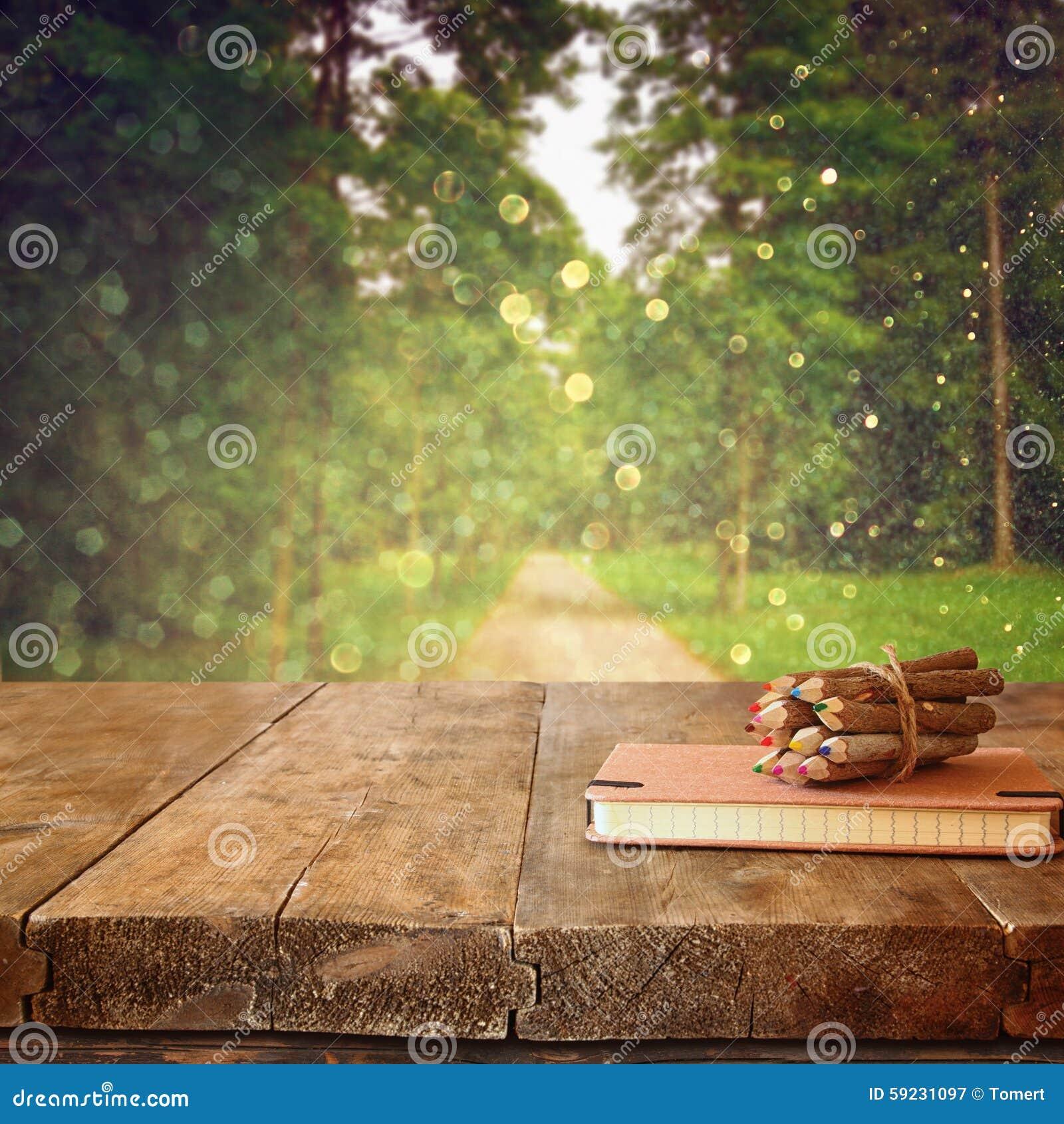 Cuaderno del vintage y pila de lápices coloridos de madera en la tabla de madera de la textura delante de la opinión del bosque d