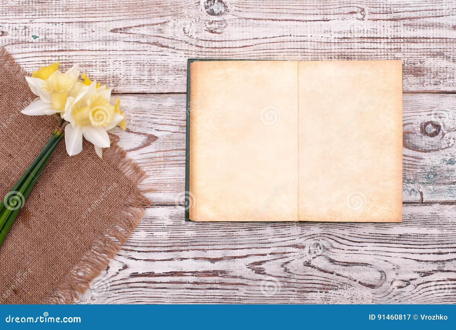 Cuaderno en blanco con la flor en la opinión superior del fondo de madera de la tabla del vintage