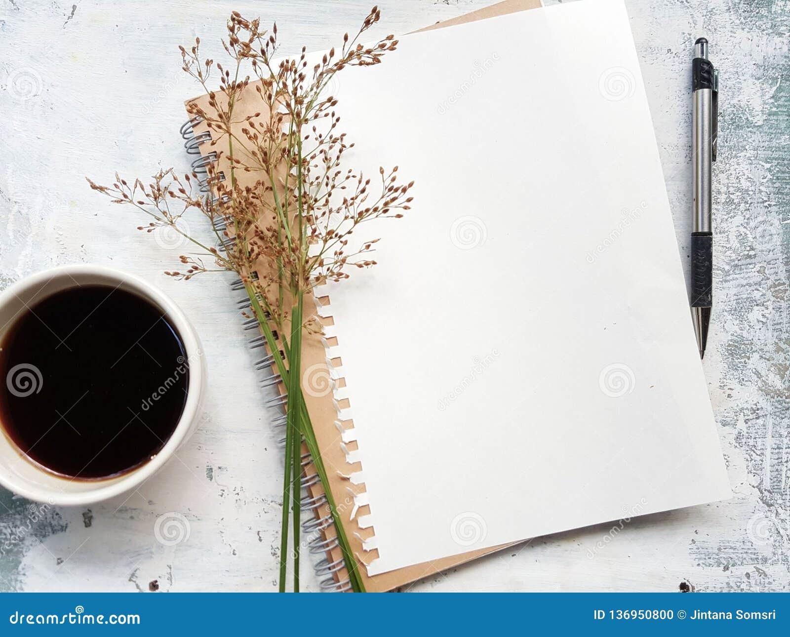 Cuaderno en blanco con la pluma al lado de una taza de café