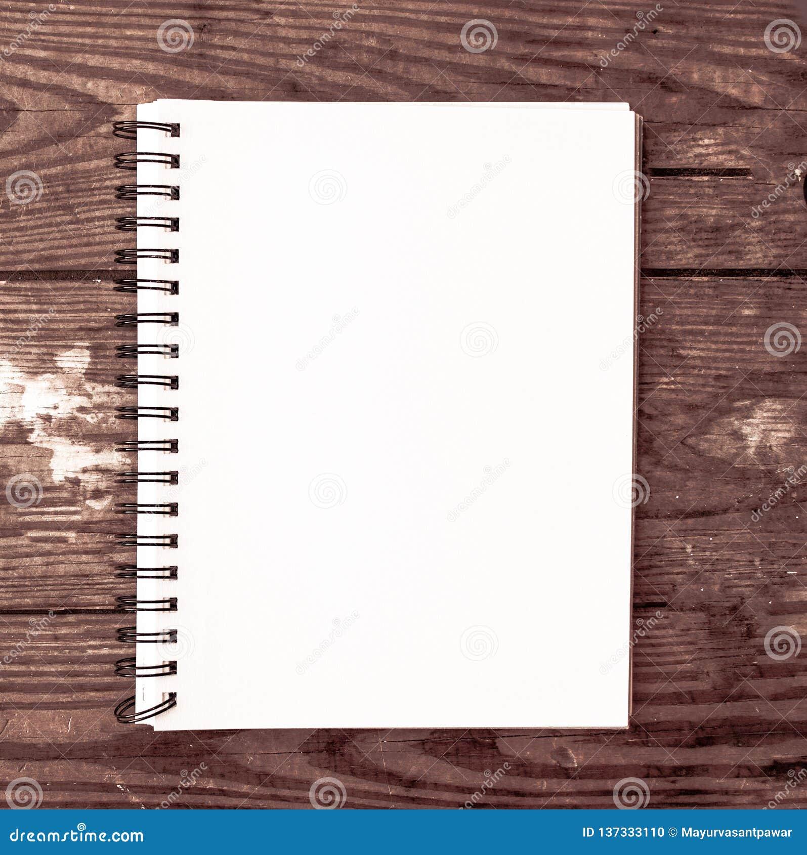 Cuaderno llano blanco para el poste de comercialización de los medios sociales con el fondo de madera