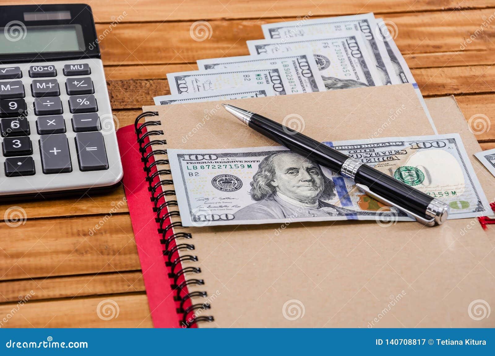 Cuaderno, pluma, dólares y una calculadora en un fondo de madera