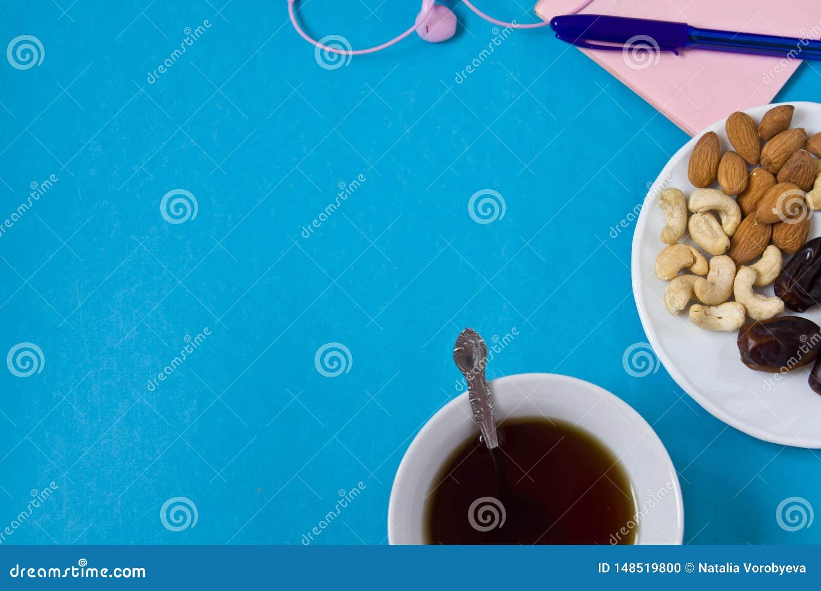 Cuaderno, pluma, flores, platillo con las frutas secadas en un fondo azul, el lugar de trabajo de las mujeres