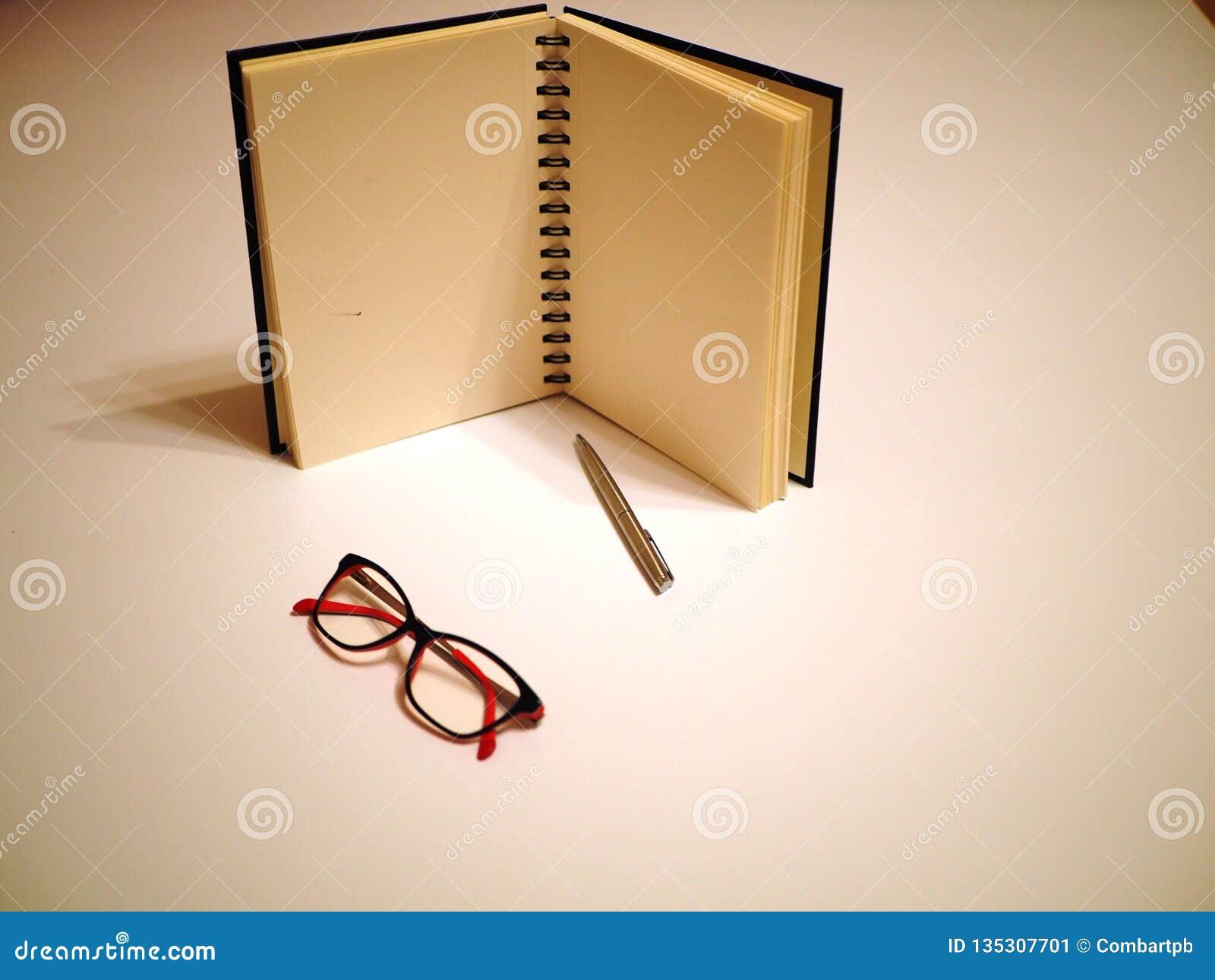 Cuaderno, pluma y vidrios en una tabla blanca