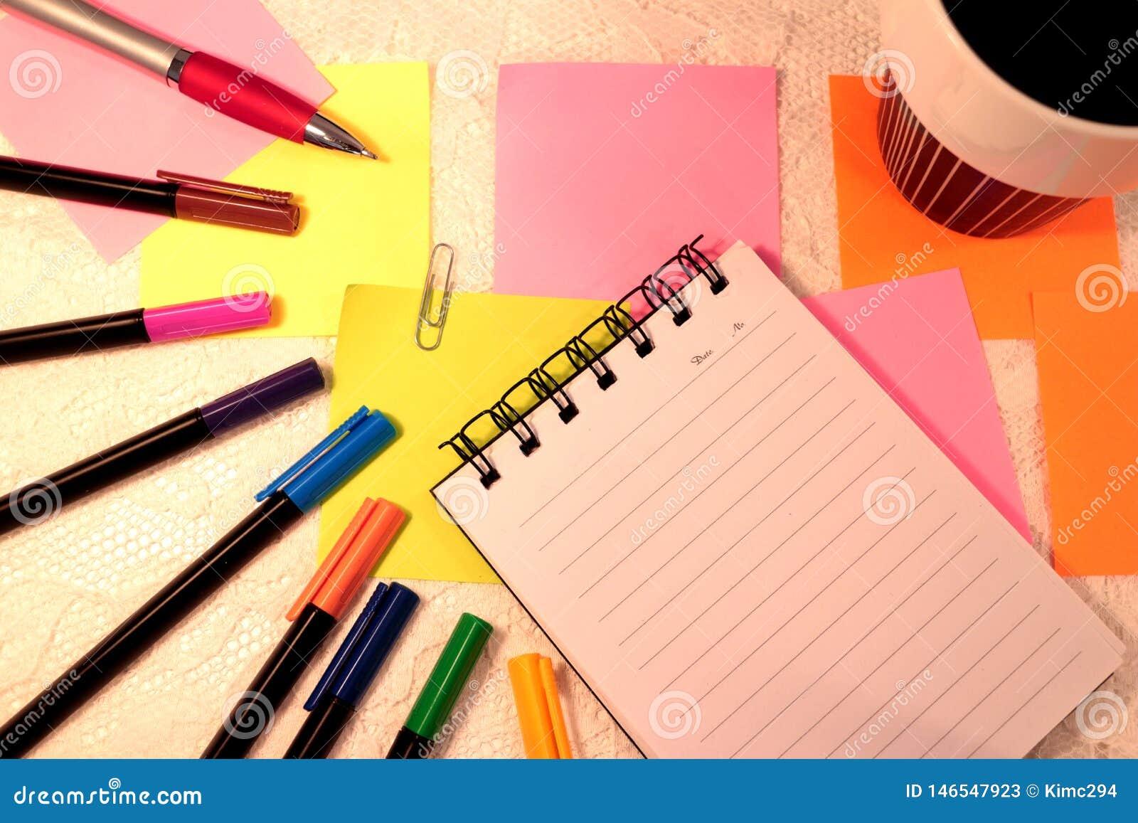 Cuaderno, plumas del fieltro en diversos colores, notas pegajosas y una taza de café