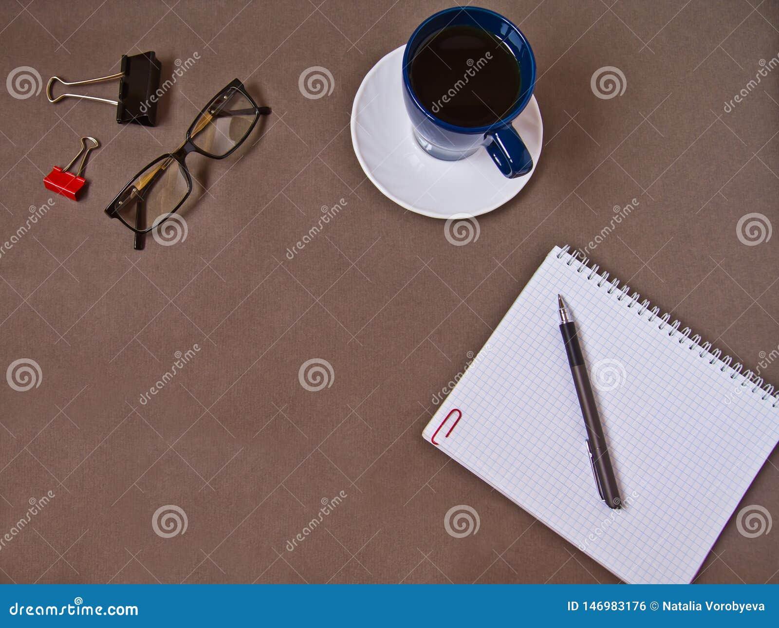 Cuaderno, taza de caf?, vidrios, materiales de oficina