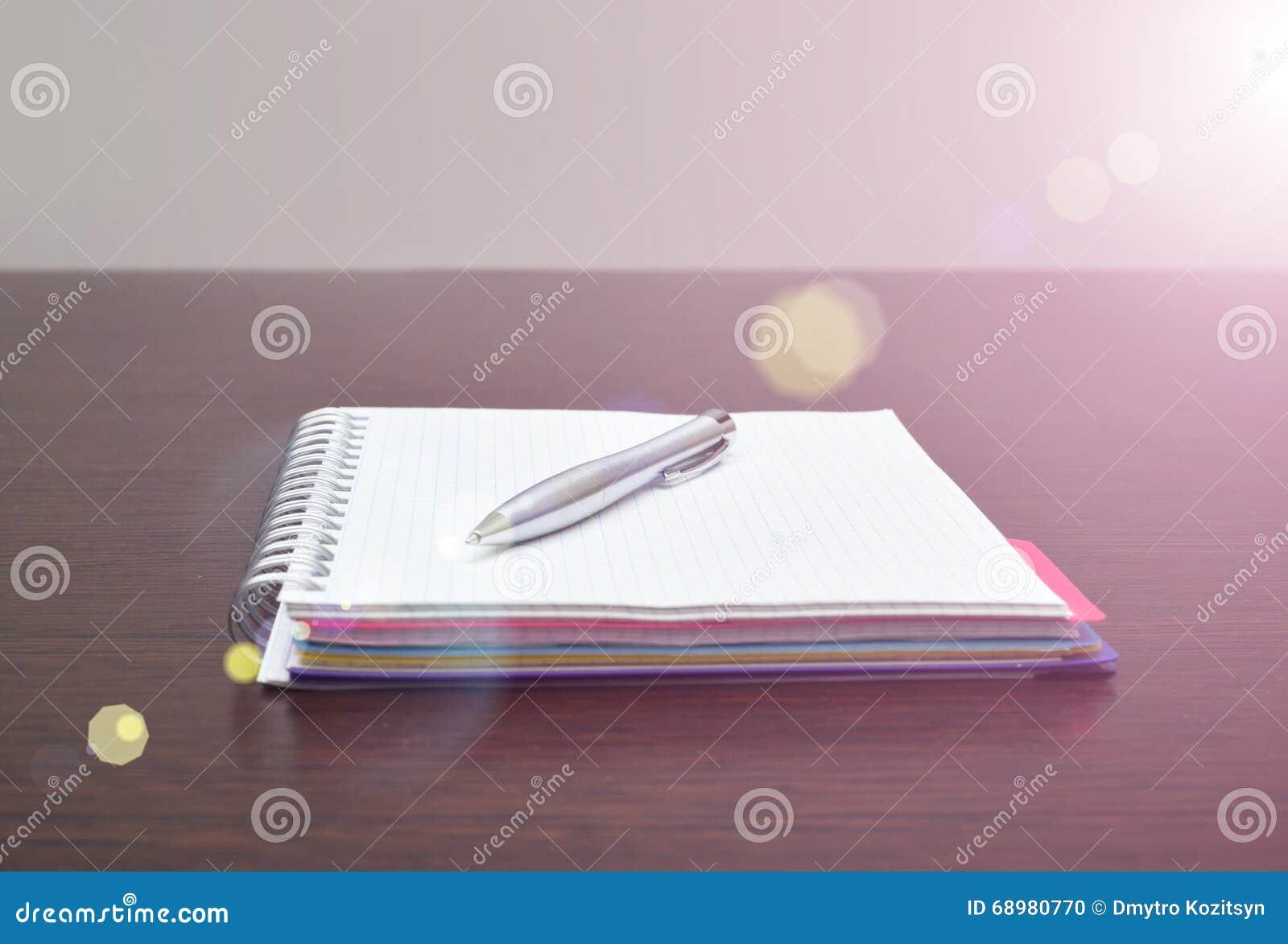 Cuaderno y pluma de acero en la tabla con luz del sol