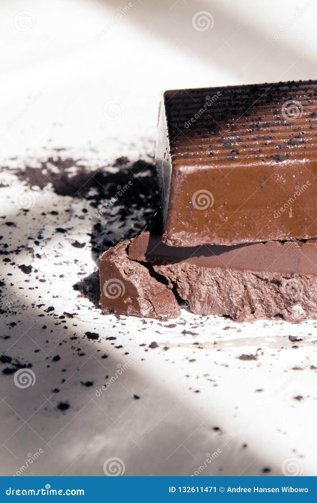 Cuadrados oscuros del chocolate apilados en tapetito con el polvo de cacao