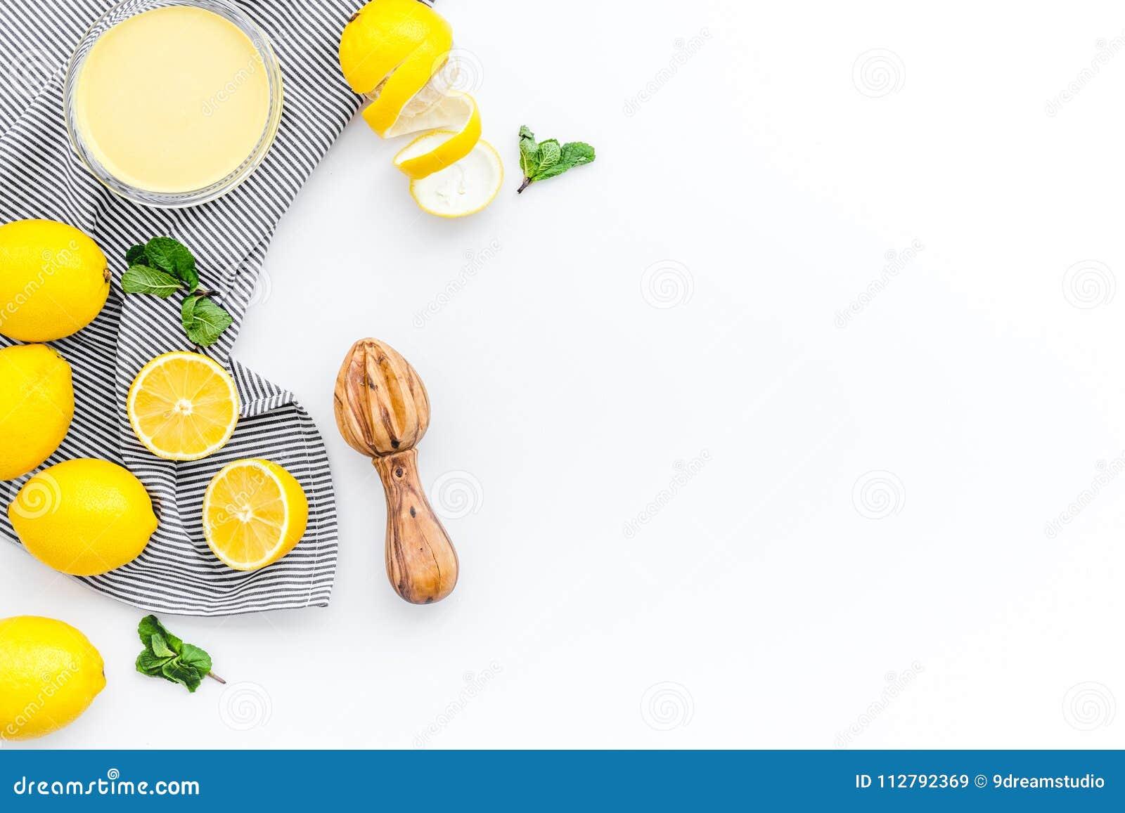 Cuajada de limón La crema dulce para los postres cerca de los limones y el juicer en la opinión superior del fondo blanco copian