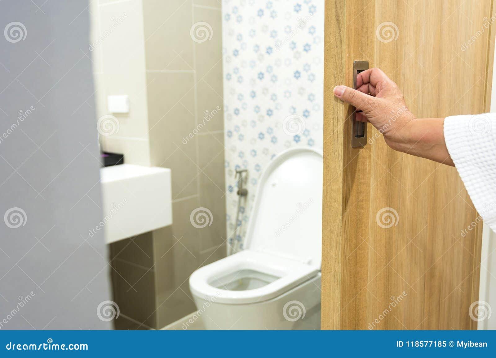 Cuarto de baño abierto de la puerta del retrete de la mano