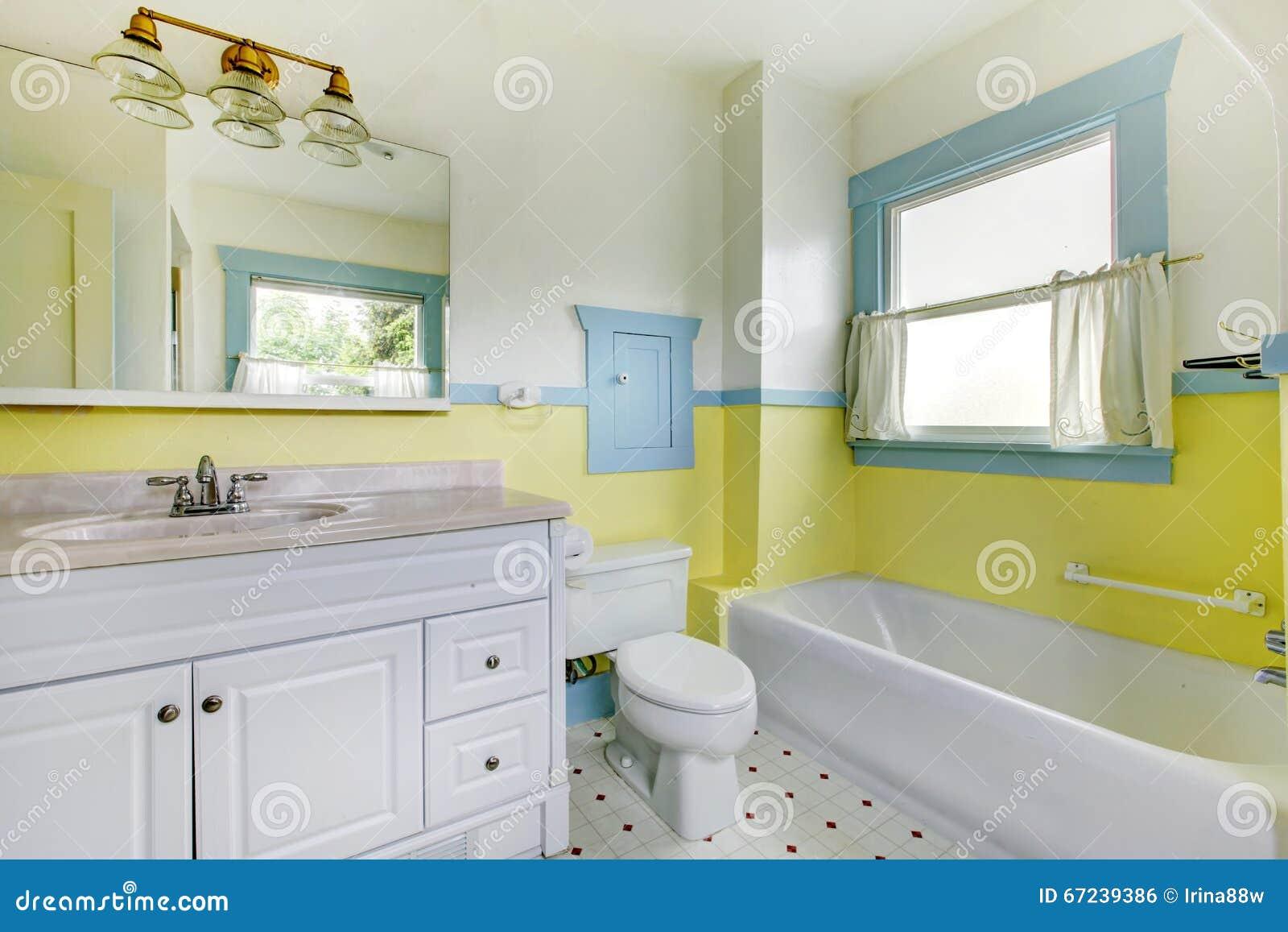 cuarto de bao con las paredes amarillas el suelo de baldosas blanco y el