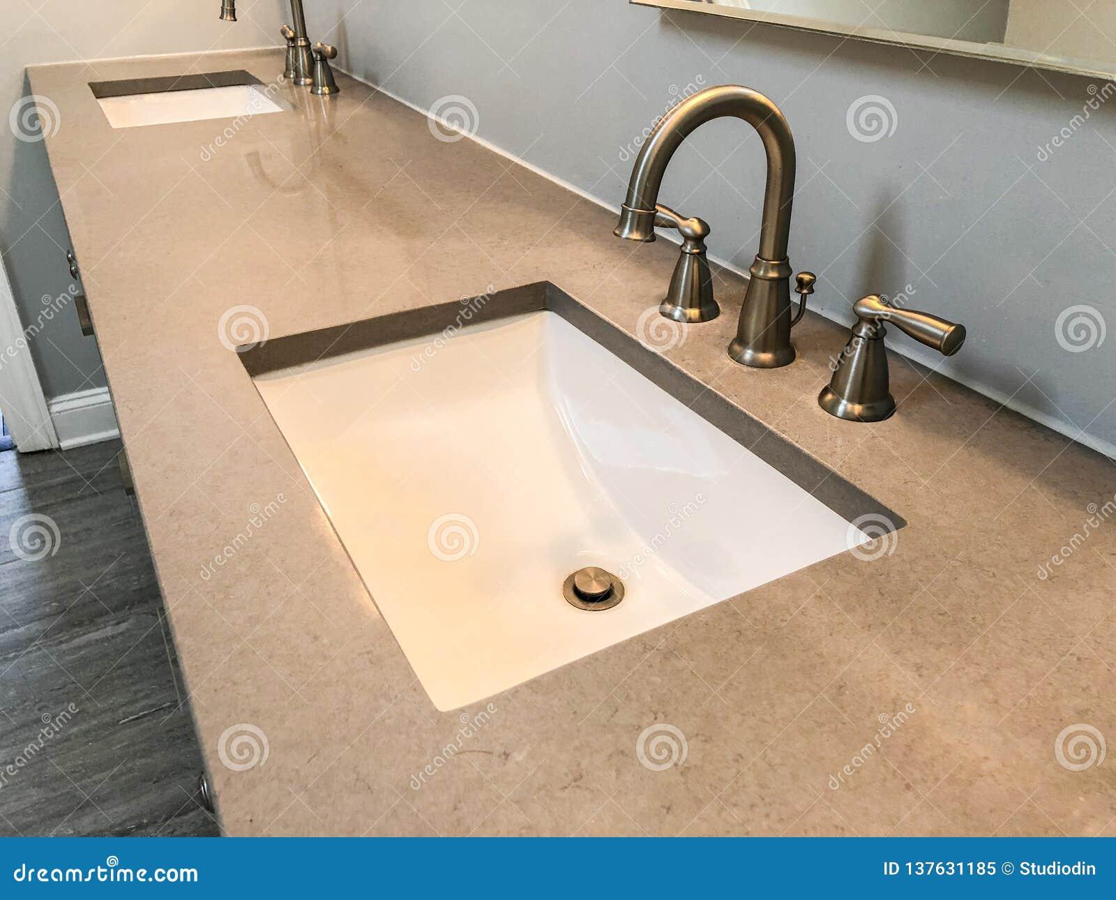 Cuarto de baño moderno con la encimera del cuarzo, dos fregaderos y grifos con el piso de piedra