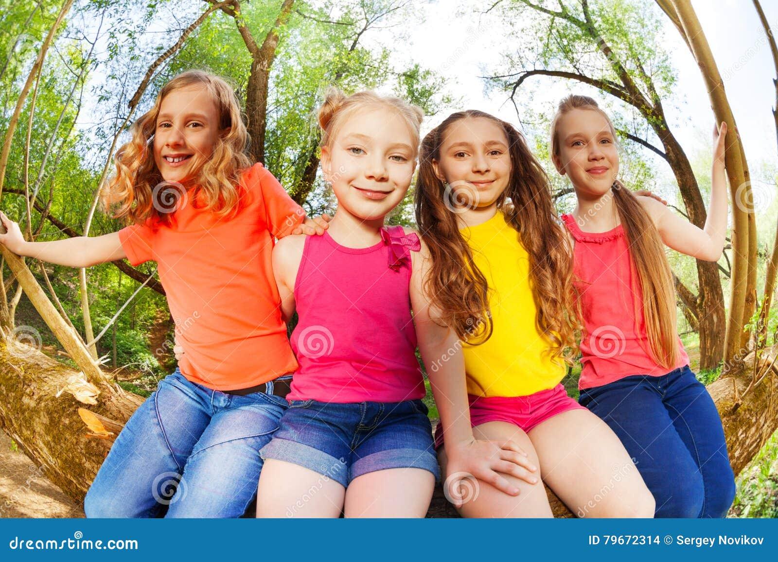 Cuatro Amigas Felices Que Se Sientan En árbol Caido Foto De Archivo