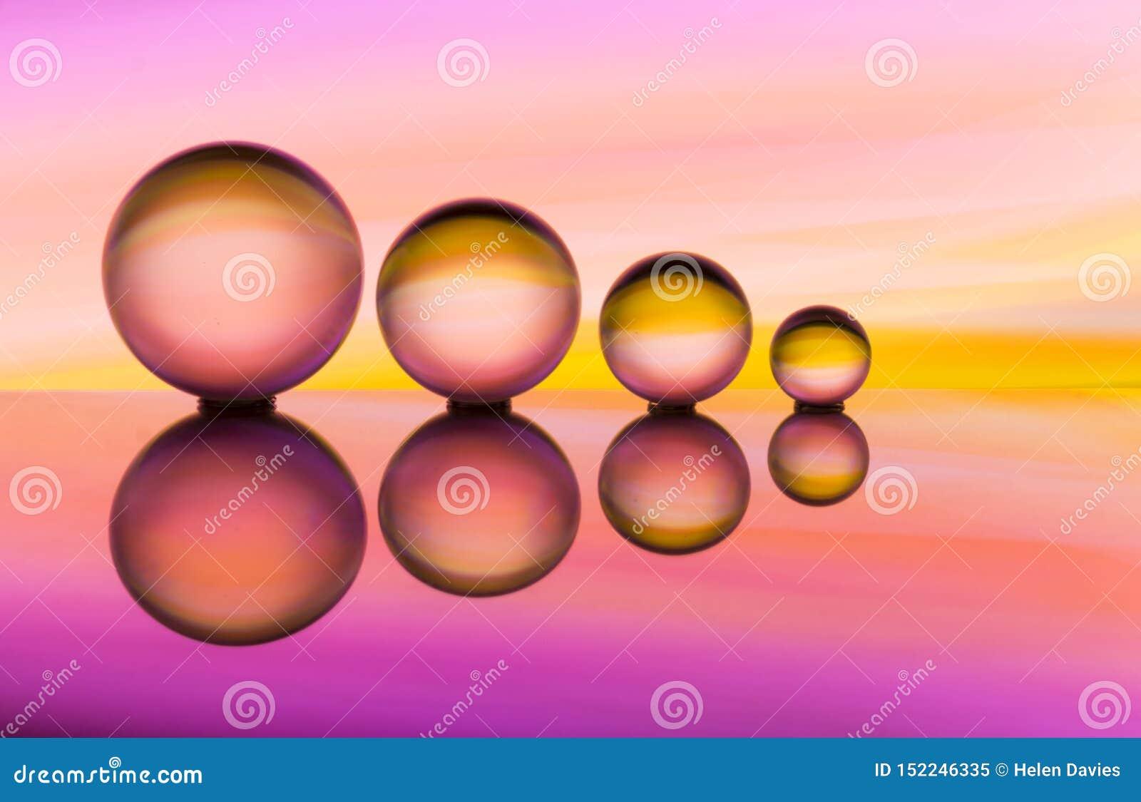Cuatro bolas de cristal en fila con las rayas coloridas del color del arco iris detrás de ellas